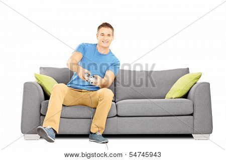 Young smiling man seated on a sofa playing video games isolated on white background