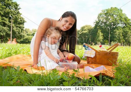 Young happy mother with daughter in the park picnicking