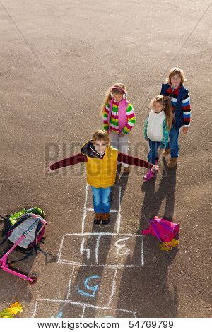 Boy With Friends Play Hopscotch