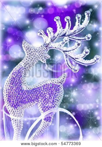 Closeup on beautiful glass reindeer decoration on purple blurry background, Christmastime festive ornament, New Year greeting card