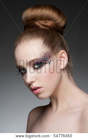 Portrait of young beautiful woman with bright fashion makeup with rhinestones and updo hairstyle