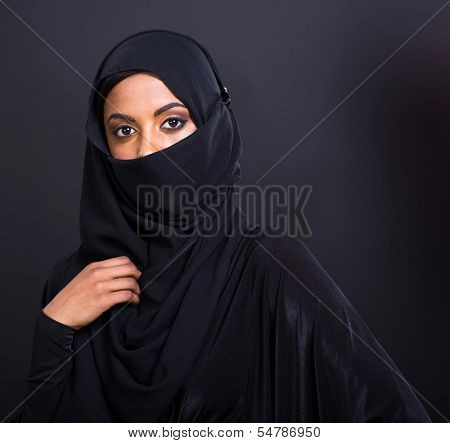 mysterious muslim woman isolated on black background