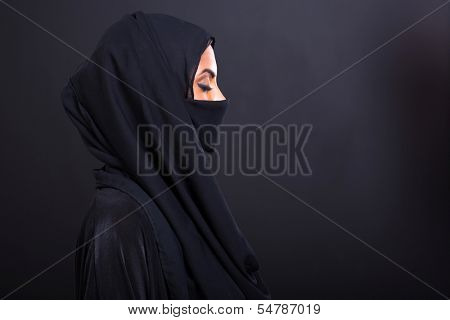 mysterious arabian woman with eyes closed on black background