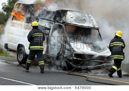 Firemen And Burning Motor Car