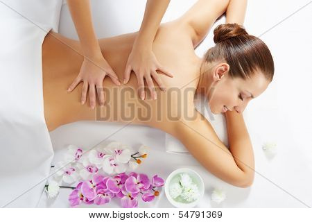 Masseur doing massage on woman face in the spa salon. Beauty treatment concept.