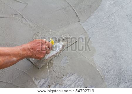 Hand using trowel on fresh concrete
