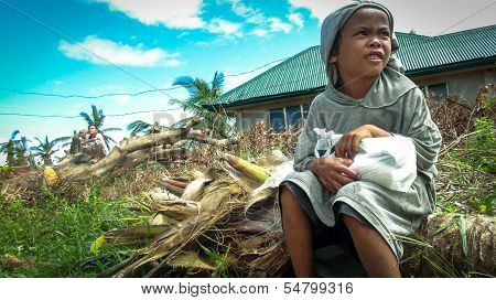 Boy Sitting On Fallen Tree Clutches Precious Food