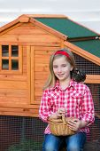 stock photo of hen house  - breeder hens kid girl rancher blond farmer playing with chicks in chicken tractor coop - JPG
