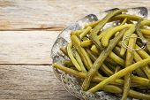 cooked green (French) beans with butter in a metal steamer basket on a rustic wooden table