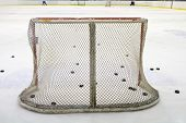 foto of bandy stick  - ice hockey net with puck on ice - JPG