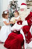 stock photo of saint-nicolas  - Saint Nicolas gives to small children Christmas gifts - JPG