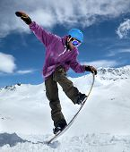 picture of snowboarding  - Snowboarder in mountains taking for the edge snowboard against the blue sky and clouds - JPG