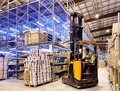 image of lift truck  - Worker in the motion on forklift in the large modern warehouse - JPG