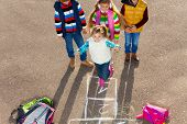 stock photo of hopscotch  - Group of three kids playing hopscotch game with girl jumping - JPG