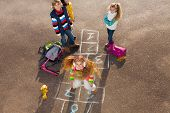 foto of hopscotch  - Happy girl jumping on hopscotch game with friends boys an girls standing by with school bags laying near - JPG