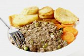 High key shot of minced beef cooked with onion, garlic, peas and herbs, served with saute potatoes a