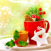Border of Christmastime utensil set, red tea cup standing on white plate and decorated with Santa Cl
