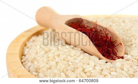stigmas of saffron in wooden bowl with spoon on white background close-up