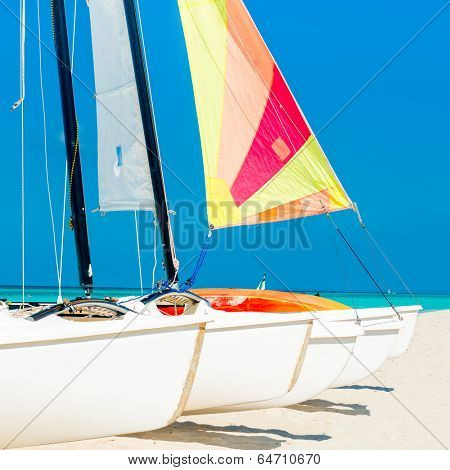 Group of catamarans with colorful sails on a tropical beach in Cuba