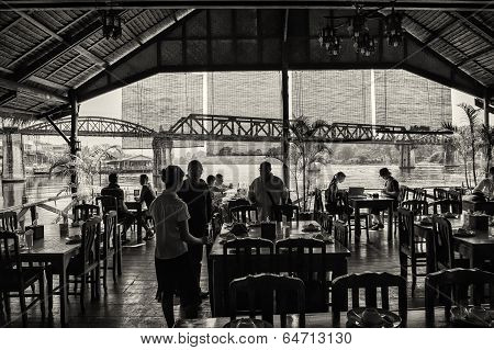 Tourists enjoy a lunch break nearby the bridge on the river Kwai