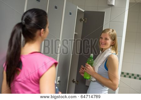 Smiling woman talking with friend in changing room at healthclub