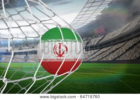 Football in iran colours at back of net against large football stadium with lights