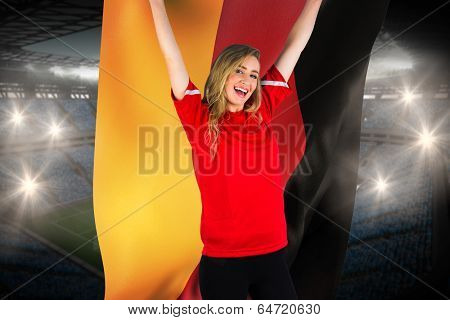 Cheering football fan in red holding germany flag against large football stadium with fans in blue