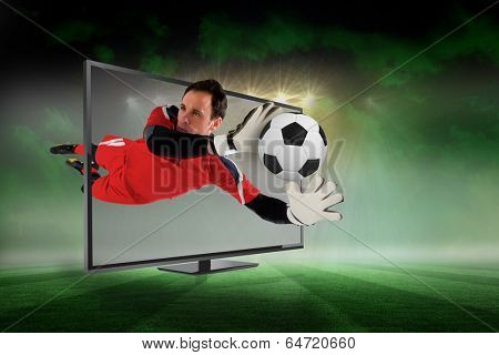 Composite image of fit goal keeper saving goal through tv against football pitch under green sky and spotlights