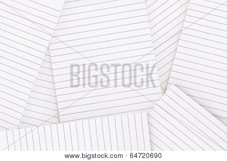 Lined notepad paper strewn over surface