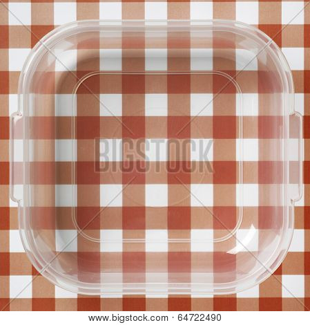Plastic Packaging Over A Red And White Tablecloths
