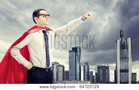 Superhero standing In front of a dark city with his fist in the air