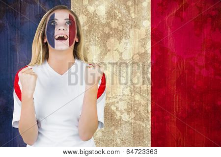 Excited france fan in face paint cheering against france flag in grunge effect