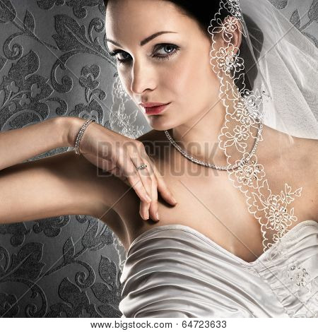 Elegant bride with diamond jewellery on vintage background