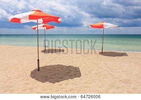 Beach Umbrellas On The Beach With Cloudy Blue Sky