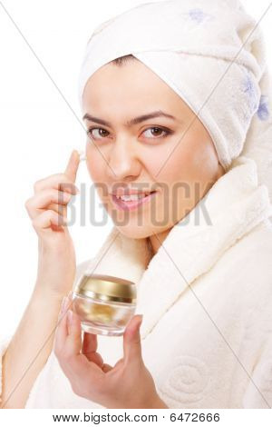 Woman In Bathrobe Applying Moisturizer