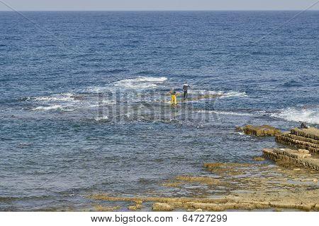 Fishermen On A Small Rocky Island