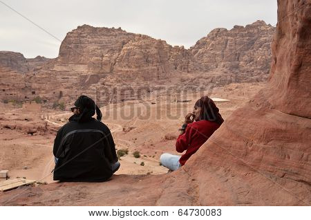Jordan, Petra. Two Men- Bedouin Sit On Edge Of A Cliff