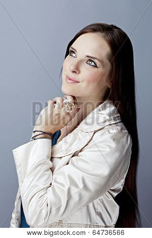 Portrait of young woman on gray studio background, wearing beige trench coat with long brunette hair