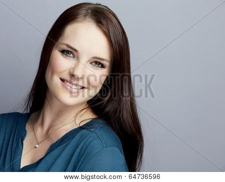 Portrait of a smiling young woman on gray studio background, wearing dark blue shirt with long brunette hair
