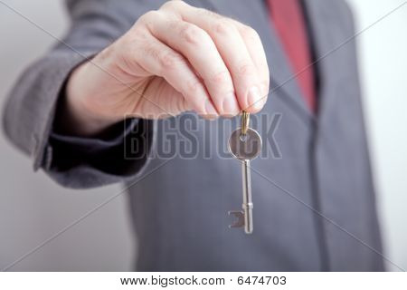 Man In Suit Holding Out Key