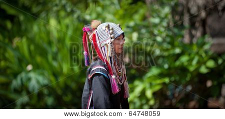 CHIANG RAI, THAILAND - DEC 4, 2013: Unidentified Akha hill tribe female in traditional clothes. Tourist travel tours to cultural villages are very popular. Folk costumes and jewelry