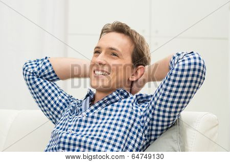 Happy Young Man With Hand Behind Head Contemplating