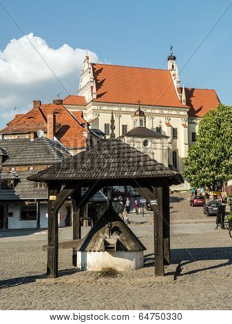 KAZIMIERZ DOLNY, POLAND - MAY 01 2014: Kazimierz Dolny town square with historical wooden well in the center surrounded by picturesque medieval houses and Parish Church Fara on the hill