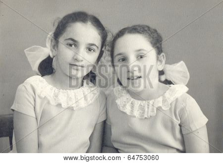studio portrait of a little sisters.