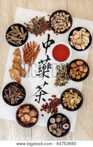 Chinese herbal tea selection and cup on rice paper over light oak wood. Translation of calligraphy script reads as chinese herbal tea.