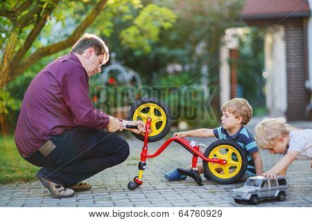 Two Little Sibling  Boys Repairing Bicycle Wheel With Father