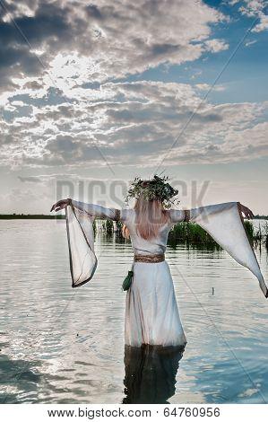 Beautiful woman with flower wreath in watet