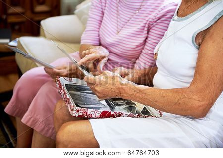 Cropped shot of elderly women feeling nostalgic and looking at old photographs