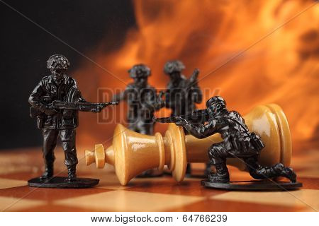 Toy soldiers kill chess King in fire.