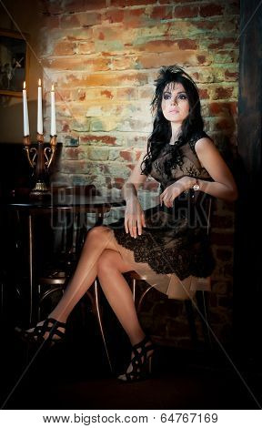 Young beautiful brunette woman in elegant lace dress sitting near a table with candlestick